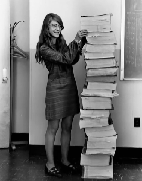 Margaret Hamilton standing next to the printout of the code used to land the Apollo 11 lunar lander. Source: NASA